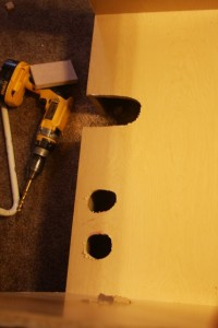 Plumbing holes drilled in the old cabinet